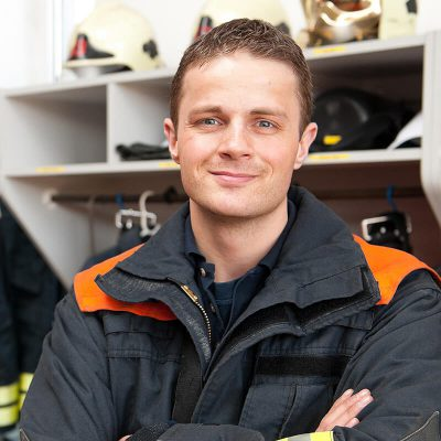 A happy firefighter looking ready for duty.