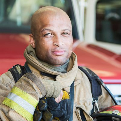 A handsome firefighter sweating while standing in front of his truck.