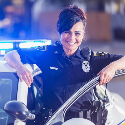 A happy police woman standing next to her police car.